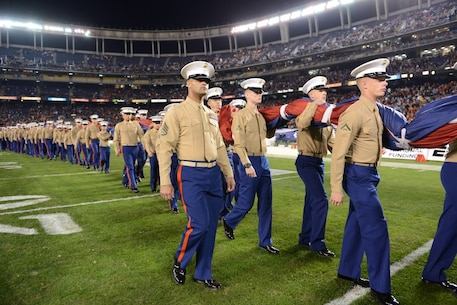 Approximately 250 Marines carry the Big Flag onto the field of Qualcomm Stadium at San Diego, Calif., during the pre-game show of the 38th annual Holiday Ball Dec. 30, 2015. The flag, weighing 850 pounds, spans the entire field and requires a minimum of 250 people to support it while unfurled. The Marines are with I Marine Expeditionary Force at Marine Corps Base Camp Pendleton and Marine Corps Air Station Miramar. The University of Wisconsin Badgers emerged victorious over the University of Southern California Trojans with a final score of 23-21. (U.S. Marine Corps photo by Lance Cpl. Timothy Valero)