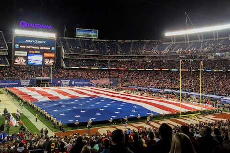Marines unfurl the Big Flag during the pre-game show of the 38th annual Holiday Bowl at Qualcomm Stadium in San Diego, Calif., Dec. 30, 2015. It takes a minimum of 250 people to present the 850 pound flag, which spans 100 yards by 50 yards, covering the entire field. The Marines are with I Marine Expeditionary Force at Marine Corps Base Camp Pendleton and Marine Corps Air Station Miramar. The University of Wisconsin Badgers emerged victorious over the University of Southern California Trojans with a final score of 23-21. (U.S. Marine Corps photo by Lance Cpl. Caitlin Bevel)