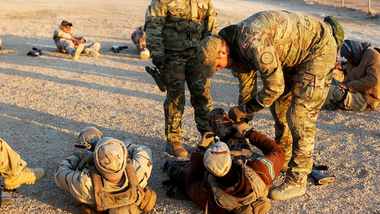 Members of the Royal Danish Army, attached to Task Force Al Asad, instruct Iraqi Security Forces in the proper way to apply a tourniquet during a combat life saver course at Al Asad Air Base, Iraq, Dec. 29, 2015.  The task force has trained approximately 2,700 Iraqi soldiers with the 7th Iraqi Army Division through the building partner capacity program. By enabling Iraqi Security Forces through advise and assist, and building partner capacity missions, the Combined Joint Task Force – Operation Inherent Resolve's multinational coalition is helping the Government of Iraq to set the conditions to defeat the Islamic State of Iraq and the Levant.