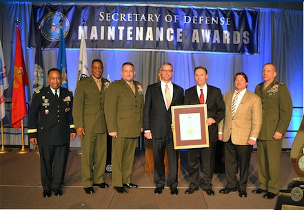 Marine Depot Maintenance Command, Marine Corps Logistics Command receives the Robert T. Mason award during the 2015 DoD Maintenance Symposium held on 08 December, 2015, in Phoenix Arizona.  Colonel Jeffrey Hooks, MDMC Commander, Mr. Trent Blalock, MDMC Deputy Commander, Mr. Rick Pavlik, TMDE Director, and Mr. John Distefano, AFGE 2317 President, accepted the award on stage for MDMC. The award was presented by General Dennis Via, Commanding General, Army Material Command.  The MDMC team was flanked on stage by Lieutenant General Michael Dana, Deputy Commandant, Installations and Logistics, and Major General Craig Crenshaw, Commanding General, Marine Corps Logistics Command.