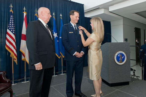 Rebecca Weaver Clarke fastens the retirement pin to the uniform of her spouse, Lt. Gen. Stanley E. Clarke III during his retirement ceremony at the Air National Guard Readiness Center, Joint Base Andrews, Md., December 18. 2015. Clarke is the 15th director of the ANG and retired after 34 years of service. (Air National Guard photo by Master Sgt. Marvin R. Preston/Released)