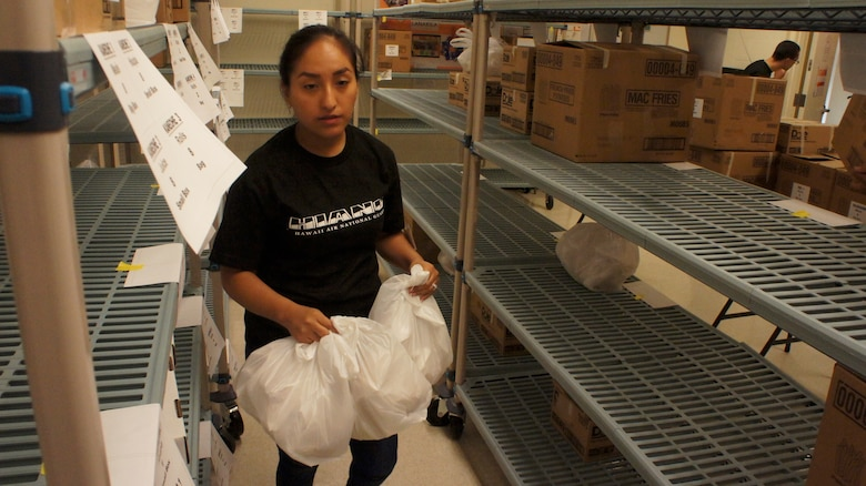 Airman 1st Class Myra Zevallos,154th Logistics Readiness Squadron sorts meals for distribution while volunteering for Lanakila Meals on Wheels, Dec. 25, 2015, Honolulu. Over 700 meals where delivered to home bound elderly on the island of Oahu on Christmas morning. Lanakila Pacific is a nonprofit organization that builds independence for thousands of people living challenged lives. Members of the Hawaii Air National Guard have been assisting in the many phases of meal preparation and delivery for over 10 years. (U.S. Air National Guard photo by Tech. Sgt. Andrew Jackson/released)