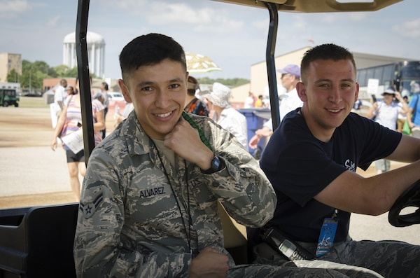 Air Force Airman 1st Class Javier Alvarez and Senior Airman Dylan Nuckolls, 11th Wing Public Affairs photojournalist, drive a golf cart around the 2015 Joint Base Andrews Air Show Sept. 19, 2015. Alvarez is one of 20 Basic Photojournalist Course students from the Defense Information School who augmented members of the JB Andrews Public Affairs staff during the air show. The students facilitated civilian media access, aided visitors from the information booths and took photos of visitors and air show performances.
