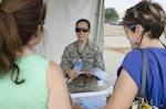 Air Force Tech. Sgt. Vanessa Reed talks with visitors of the 2015 Joint Base Andrews Air Show, Md., Sept. 19, 2015. Reed is one of 20 Basic Photojournalist Course students from the Defense Information School who augmented members of the JB Andrews Public Affairs staff during the air show. The students facilitated civilian media access, aided visitors from the information booths and took photos of visitors and air show performances.