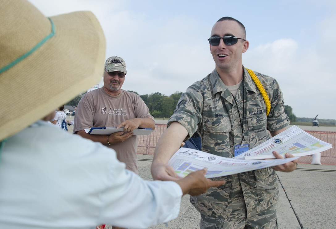 Air Force Airman 1st Class Travis Biehl hands a map to a visitor of the 2015 Joint Base Andrews Air Show Sept. 19, 2015. Biehl is one of 20 Basic Photojournalist Course students from the Defense Information School who augmented members of the JB Andrews Public Affairs staff during the air show.