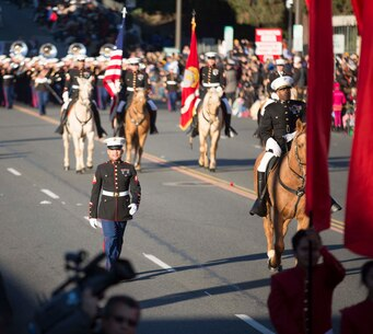 Sgt. Xzavier Wolef, career planner, MCLB Barstow, walks along side Col. Sekou Karega, commanding officer, MCLB Barstow, during the 127th Tournament of Roses Parade, in Pasadena, Calif. Jan.1, 2016. Following are the Marine Corps Mounted Color Guard and the United States Marine Corps West Coast Composite Band out of San Diego.