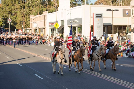 The Marine Corps Mounted Color Guard, from Marine Corps Logistics Base Barstow, leads the United States Marine Corps West Coast Composite Band, from San Diego, down Colorado Boulevard,Pasadena, Calif., during the 127th Tournament of Roses Parade, Jan. 1, 2016.