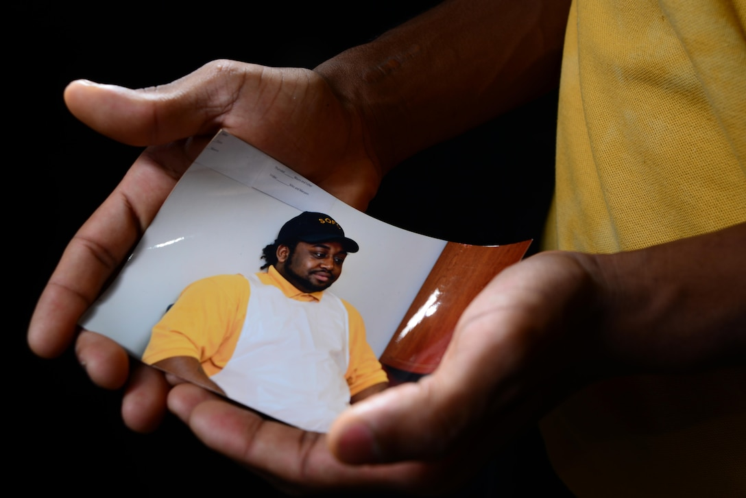 Kendall L. Mountain holds a photo of his older brother, Marcus, who was killed in a 2012 car accident. Kendall works at the Freedom Inn Dining Facility at Fort Meade, Md., where Marcus worked at the time of the accident.