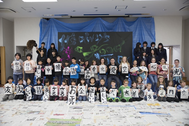 Marine Corps Air Station Iwakuni home-schoolers pose for a group picture with the Calligraphy Club from Kannon High School, Hiroshima, during a calligraphy event at the Waki General Community Center in Waki Town, Japan, Jan. 4, 2016. This event allowed the home-schoolers to learn about the culture that they are now a part of. Community relations events like these help bolster the relationship between the station and the local Japanese community.