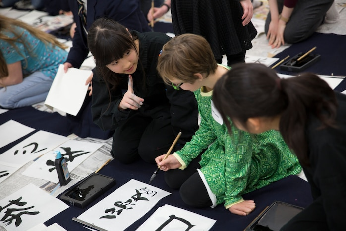 Mihiro Yamamoto, a member of the Calligraphy Club at Kannon High School, Hiroshima, Japan, teaches a home-schooler from Marine Corps Air Station Iwakuni how to write calligraphy during a calligraphy event at the Waki General Community Center, Waki Town, Jan. 4, 2016. Station residents and local residents only grow closer with each of these events.
