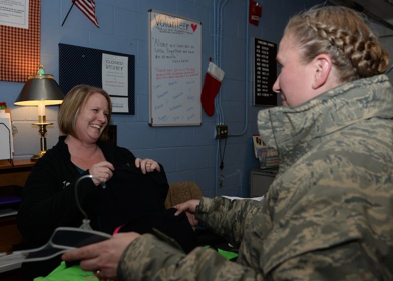 Jennie Mason, B-One Thrift Store assistant supervisor, takes clothing off hangers for Tech. Sgt. Jessica Nicholson, 28th Aircraft Maintenance Squadron vehicle control noncommissioned officer, at Ellsworth Air Force Base, S.D., Dec. 18, 2015. The thrift store has three programs created to assist Airmen in need of household goods or clothing. For more information about the B-One Thrift Store and its programs, call (605) 385-5383. (U.S. Air Force photo by Airman Sadie Colbert/Released)