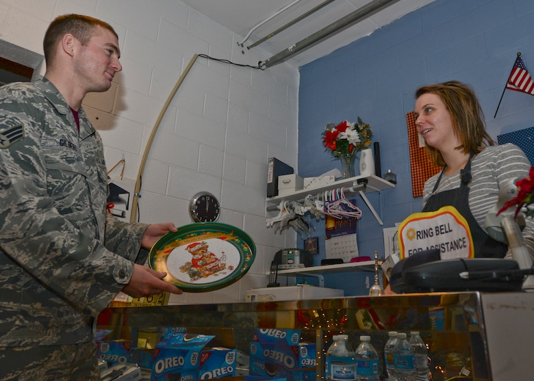 Senior Airman Brandon Gilbert, 28th Contracting Squadron specialist, left, hands a cookie platter to Magan Powell, B-One Thrift Store assistant manager, at Ellsworth Air Force Base, S.D., Dec. 18, 2015. The thrift store has three programs created to assist Airmen in need of household goods or clothing. For more information about the B-One Thrift Store and its programs, call (605) 385-5383 (U.S. Air Force photo by Airman Sadie Colbert/Released)