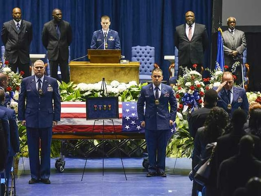 Annie McBride is saluted after her son, Air Force Staff Sgt. and Special Agent Chester McBride, is posthumously awarded four medals for his actions and service by Air Force Office of Special Investigations officials during McBride's funeral at Georgia Southern University's Hanner Fieldhouse Jan. 2. (Photo courtesy Statesboro Herald.com)
