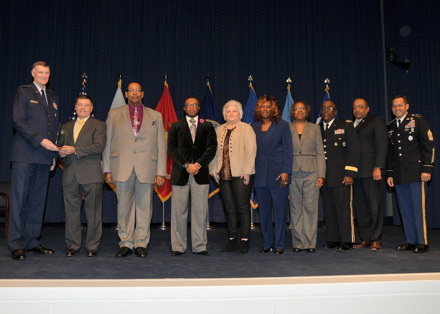DLA director Air Force Lt. Gen. Andy Busch, left, presents the DLA Distribution Red River, Texas, Equal Employment Office team (left to right: Kirby Olson, Willie Houff, Kacy Harvey, Gina Edwards, Melba Golston and Jo Linda Warren) the Outstanding Achievement in EEO award at the 48th annual employee recognition ceremony Dec. 10.  Distribution's commander Army Brig. Gen. Richard Dix, third from right, DLA's equal employment opportunity director Ferdinand LeCompte, second from right, and DLA's Senior Enlisted Leader Army Command Sgt. Maj. Charles Tobin, right, were also on-hand to present the award.  (Photo by Teadora Mocanu)