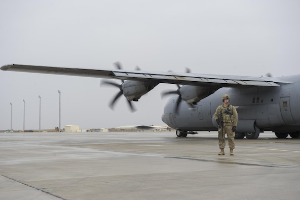 Staff Sgt. Tyler Berogan, a 455th Expeditionary Security Forces Squadron Fly Away Security Team member, provides security as a C-130J Super Hercules is unloaded at Camp Bastion, Afghanistan, Jan. 3, 2016. The 455th ESFS FAST is the all-encompassing security team that provides ground safety and cockpit denial to protect the aircraft and crew. (U.S. Air Force photo/Tech. Sgt. Robert Cloys)