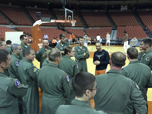 Members of the 435th Fighter Training Squadron engage in a full-court discussion with Shaka Smart, head coach of the University of Texas men's basketball team, 19 Nov. 2015 at the UT basketball stadium. The Deadly Black Eagles met with the coach to discuss building relationships within a team and leadership philosophies. (Courtesy photo)