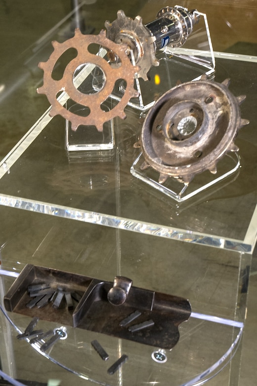This bicycle sprocket hub and sprockets from the Wright Bicycle Co. are on display at the National Museum of the United States Air Force. The Wrights later used a bicycle-type chain drive in their early airplanes. Also on display are a composting stick and metal type from the Wright printing business.