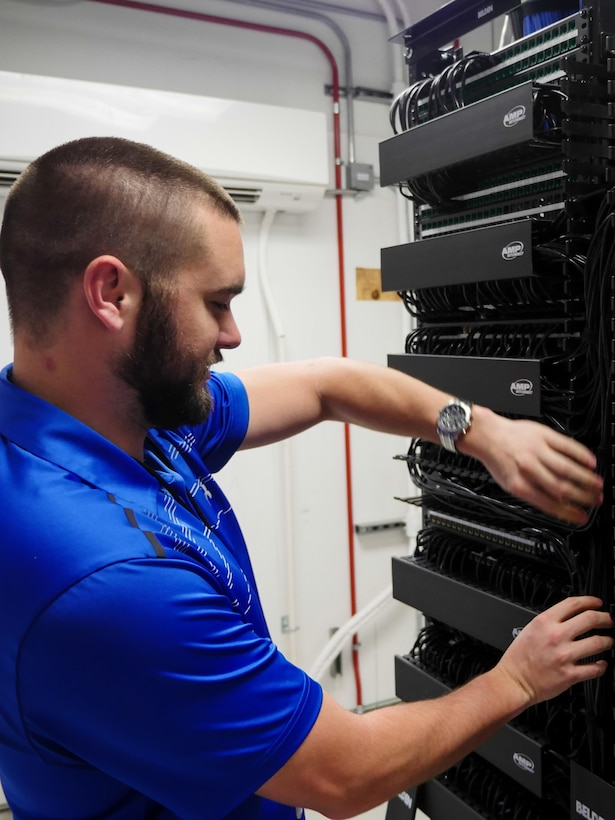 Chris Kish, technician, inspects a communications closet at the Defense Information School on Fort Meade, Md., Jan. 7, 2016. The IT team led the effort to plan and execute the successful running of 236.2 miles of cable, installation of 1,978 data drops and 450 phone drops, and the transfer of 2,400 computer systems from south campus to the main campus to prepare for training in the new wing.