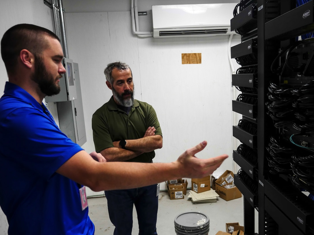 Chris Kish, technician, discusses port availability in a communications closet with Rob Phelps, Defense Information School information technology operations manager, at DINFOS on Fort Meade, Md., Jan. 7, 2016. The IT team led the effort to plan and execute the successful running of 236.2 miles of cable, installation of 1,978 data drops and 450 phone drops, and the transfer of 2,400 computer systems from south campus to the main campus to prepare for training in the new wing. (DoD photo by Joseph Coslett/Released)
