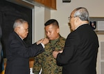 Marine Corps Master Gunnery Sgt. Phu Cao is pinned with his new rank by his father Ty Huu Cao, left, and father-in-law Tu Van, right, during his promotion ceremony Jan. 5 in the McKeever Auditorium on Defense Supply Center Richmond, Virginia.  Cao is currently serving a joint assignment as the senior non-commissioned officer-in-charge for Defense Logistics Agency Aviation's Marine Aviation Cell.