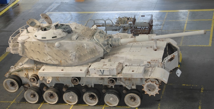 Genesis II, an M60A1 Main Battle Tank, sits in the craneway of Marine Depot Maintenance Command waiting to be refurbished as part of a restoration project between MDMC and the National Museum of the Marine Corps, Sept. 5, 2015. Genesis II and it crew, attached to Company C, 3rd Tank Battalion, Twentynine Palms, Calif., spearheaded the Marine attack on the Southern frontier of Kuwait during the opening moments of Operation Desert Storm, earning a permanent place in the museum.