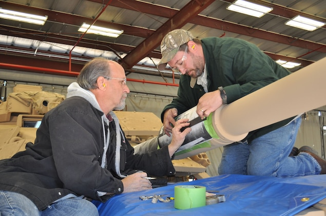 Marine Depot Maintenance Command artisans stencil the gun barrel of the Genesis II, an M60A1 Main Battle Tank, as part of the final steps in a restoration project between MDMC and National Museum of the Marine Corps, Dec. 15, 2015.