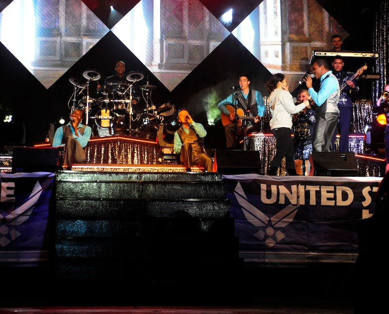 """Tops in Blue members sing to an audience member during a performance on the 2015, """"Freedom's Song"""" world tour, Jan. 6, 2016, at Incirlik Air Base, Turkey. Tops in Blue visited Incirlik AB as part of their seven-month tour, which includes 75 shows in 20 different countries.  (U.S. Air Force photo by Senior Airman Krystal Ardrey)"""