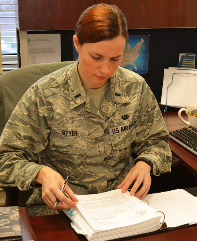 1st Lt. Hilary Styer, the 111th Attack Wing's full-time staff judge advocate, prepares her workspace upon taking on the new role January 5, 2015, at Horsham Air Guard Station, Pennsylvania. Styer is a Pennsylvania native who served as a lawyer in the civilian sector before joining the Pa. Air National Guard. (U.S. Air National Guard photo by Tech. Sgt. Andria Allmond/Released)