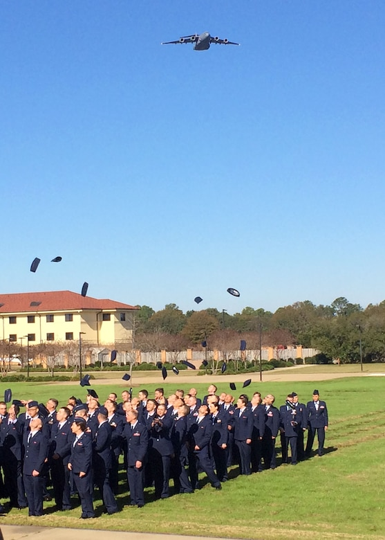 A C-17 Globemaster III flies overhead as newly commissioned 120th Airlift Wing 2nd Lieutenants Matthew Hall, Alissa Engel, Bradford Lewis, and Joshua Briggs join fellow classmates in throwing their hats into the air in celebration of their graduation from Officer Training School at Maxwell Air Force Base, Ala. Dec. 18, 2015. (U.S. Air National Guard photo by Capt. Kenneth Fechter/Released)