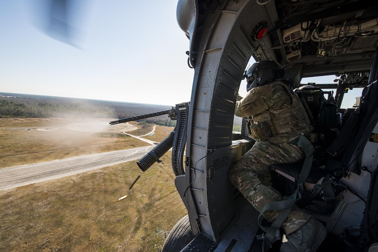 Tech. Sgt. Uwemediimo Essien fires a .50-caliber machine gun at simulated enemy targets while flying over Grand Bay Bombing and Gunnery Range Feb. 19, 2015, at Moody Air Force Base, Ga. The side-mounted, .50-caliber machine gun is the HH-60G Pave Hawk's primary form of defense. Essien is a 41st Rescue Squadron aerial gunner. (U.S. Air Force photo/Senior Airman Ryan Callaghan)