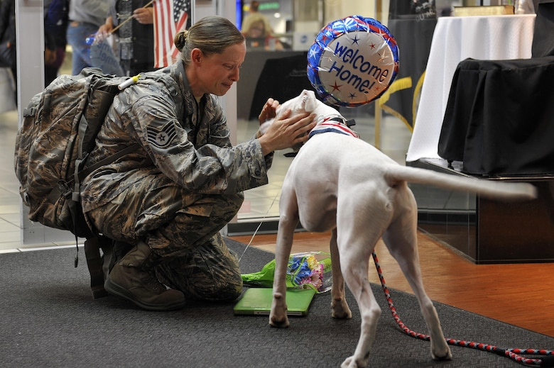 Staff Sgt. Arin Vickers, assigned to the 435th Supply Chain Operations Squadron, is greeted by her dog when she arrives at an airport USO in St. Louis on May 6, 2015. Vickers was gone for six months, and her friends and family were there to greet and surprise her by bringing along Baxter. (U.S. Air Force photo/Airman 1st Class Erica Crossen)