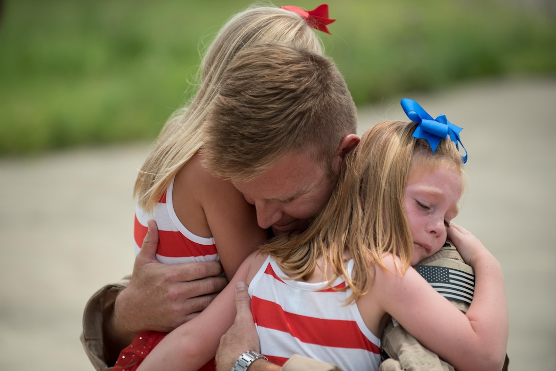 Capt. Ross Farling, a C-130 Hercules pilot from the 123rd Airlift Wing, hugs his daughters during a homecoming ceremony in Louisville, Ky., July 4, 2015. Farling was among 39 guardsmen who returned from a deployment to the Persian Gulf region, where they supported Operation Freedom's Sentinel. (U.S. Air National Guard photo/Maj. Dale Greer)