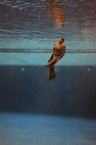 A security forces Airman plunges into the combat water survival test at the U.S. Air Force Academy, Colo., July 17, 2015. The event was part of a daylong course for Airmen across the Front Range area to determine if they are physically and mentally ready to attend the U.S. Army Pre-Ranger Training Assessment Course, a prerequisite to attending the U.S. Army Ranger School at Fort Benning, Ga. (U.S. Air Force photo/Jason Gutierrez)