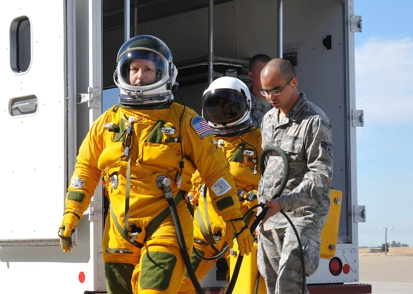 Secretary of the Air Force Deborah Lee James walks to a U-2S as Senior Airman Aaron Saenz, a 9th Physiological Support Squadron launch and recovery technician, carries the high-altitude pressure suit auxiliary equipment at Beale Air Force Base, Calif., Aug. 11, 2015. The specialized pressure suit allows U-2S pilots to safely fly at altitudes reaching 70,000 feet. James visited Beale AFB to receive a firsthand perspective of high-altitude intelligence, surveillance and reconnaissance from collection to dissemination. (U.S. Air Force photo/Senior Airman Dana J. Cable)