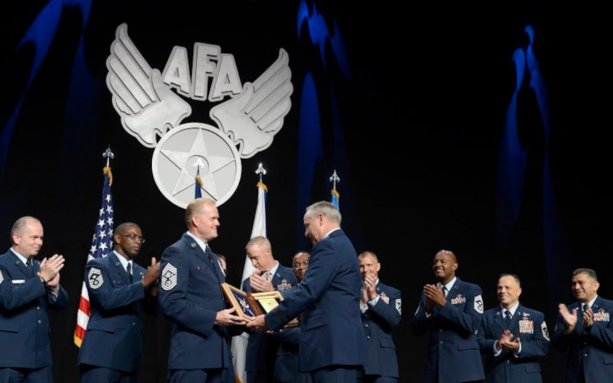 """Chief Master Sgt. of the Air Force James A. Cody thanks Air Force Chief of Staff Gen. Mark A. Welsh III for his exceptional service by presenting him with an invitation to an Order of the Sword ceremony, following his """"Enlisted Force Update"""" at the Air Force Association's Air and Space Conference and Technology Exposition Sept. 16, 2015, in Washington, D.C.  (U.S. Air Force photo/Scott M. Ash)"""