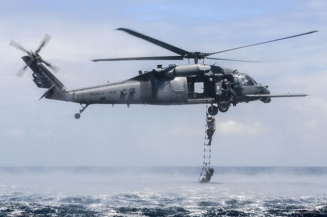 An HH-60G Pave Hawk from the 33rd Rescue Squadron at Kadena Air Base, Japan, performs a rope-ladder recovery with Airmen from the 320th Special Tactics Squadron during an amphibious operations exercise Sept. 22, 2015, off the west coast of Okinawa, Japan. Special tactics Airmen are organized, trained and equipped to conduct high-risk combat operations. (U.S. Air Force photo/Senior Airman John Linzmeier)