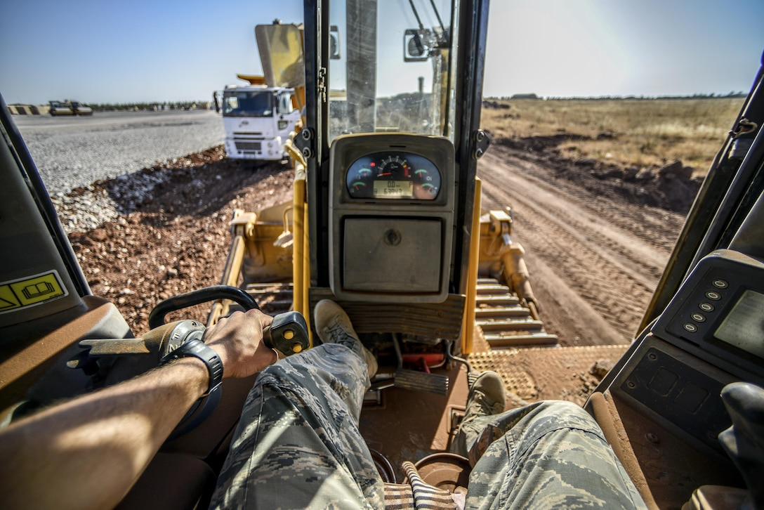 Staff Sgt. Logan Pals, a 435th Construction Training Squadron pavements and construction equipment operator, sits in the seat of a bulldozer while waiting for gravel to be dumped Sept. 24, 2015, at Diyarbakir Air Base, Turkey. The 435th CTS has more than 10 construction vehicles that are used to dump, move, grade and roll gravel throughout the base. (U.S. Air Force photo/Airman 1st Class Cory W. Bush)