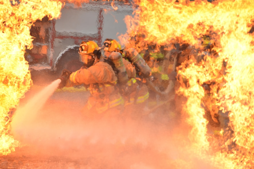 Air Force firefighters rush into extreme temperatures to extinguish a fire during training at the 165th Airlift Wing in Garden City, Ga., Oct. 3, 2015. Firefighters from the 165th AW train to meet local and global protection needs and provide timely fire prevention education and protection to the wing, the Air Dominance Center and the airport tenants. (U.S. Air National Guard photo/Staff Sgt. Noel Velez)