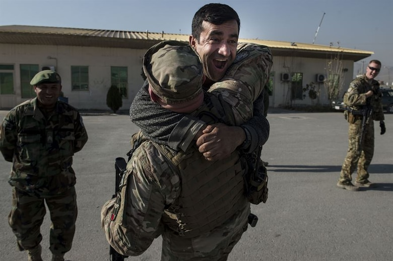 An Afghan air force member jumps into the arms of U.S. Air Force Master Sgt. Daniel Prosymchak near Forward Operating Base Oqab, Kabul, Afghanistan, Dec. 13, 2015. Prosymchak is assigned to the Train, Advise, Assist Command-Air security forces and is deployed from Joint Base Charleston, S.C. (U.S. Air Force photo/Staff Sgt. Corey Hook)