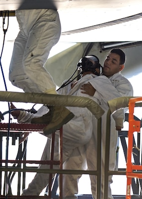 Senior Airman Eric Garcia, 433rd Maintenance Squadron aircraft fuel systems technician, removes a manikin from the wing of a C-5A Galaxy aircraft during a fuell extraction exercise Dec. 17, 2015, at Joint Base San Antonio-Lackland, Texas. The annual exercise is graded for extraction protocol, execution time, and safety. This year the Airmen completed the exercise in record time, 3 minutes and 15 seconds. (U.S. Air Force photo by Benjamin Faske/released)
