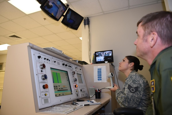Col. Michael Richards, 59th Hyperbaric Medicine Flight commander, observes as Staff Sgt. Sherri Jones, 59th HMF hyperbaric medical technician, demonstrates the controls of the mono-place hyperbaric chamber Nov. 18,2015, at the Wilford Hall Ambulatory Surgical Center, Joint Base San Antonio-Lackland, Texas. Treatments in the chamber help wounded warriors, diabetics and cancer patients recover more quickly from their ailments. (U.S. Air Force photo by Tech. Sgt. Christopher Carwile)