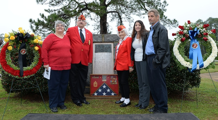 """Members of the Covella family pose for a photo in front of a bronze plaque mounted on a marble monument honoring the late Gunnery Sgt. Joseph Covella, Jan. 8. Covella was mortally wounded while serving as an advisor to the Armed Forces of the Republic of Vietnam, Jan. 3, 1966. The base pond was officially named """"Covella Pond"""" Sept. 23, 1969."""