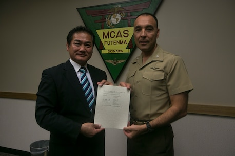 Col. Peter Lee and Ginowan Mayor Atsuchi Sakima pose for a photog Dec. 22 on Marine Corps Air Station Futenma, Okinawa, Japan. Lee and Sakima signed an extension on the Ginowan emergency vehicle and personnel access agreement. In order to save time and lives, the agreement gives Okinawan emergency vehicles and personnel base access in case of an emergency. According to Lee, commanding officer of MCAS Futenma, the agreement is just a small part of the overall partnership between the Ginowan community and the Marine Corps.