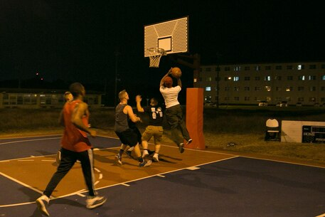 Status of Forces Agreement personnel participate in a basketball game Jan. 1 on Marine Corps Air Station Futenma, Okinawa, Japan. The basketball game provided a safe alternative to drinking on New Year's. Approximately 30 people participated in the game, which was hosted by Futenma's Single Marine Program and Navy Lt. Yonina E. Creditor, the station chaplain for MCAS Futenma. (Marine Corps Photo by Lance Cpl. Douglas D. Simons/Released)