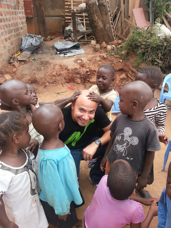 Capt. Benjamin Quintanilla, 28th Bomb Wing chaplain, center, poses for a photo with orphans from the Watoto [Swahili for 'children'] holistic care program in Uganda, Africa, Aug. 4, 2014. Quintanilla served as a missionary in Uganda for two years, caring for and rescuing orphaned and abandoned children before becoming an active duty Air Force chaplain. (Courtesy Photo)