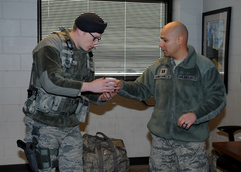 Capt. Benjamin Quintanilla, 28th Bomb Wing chaplain, right, hands a cup of hot chocolate to Airman 1st Class Taylor Tschida, 28th Security Forces Squadron response force member, at Ellsworth Air Force Base, S.D., Jan. 7, 2016. Chaplains provide many services including unit engagement as a way to boost Airmen morale. (U.S. Air Force photo by Airman 1st Class Denise M. Nevins/Released)