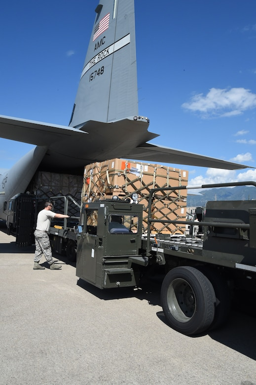 U.S. Air Force Tech. Sgt. Deavin Lee, 612th Air Base Squadron, unloads cargo from a U.S. Air Force C-130J Super Hercules  cargo aircraft on Soto Cano Air Base, Honduras, Jan. 7, 2016. The cargo was donated by Helping Hands Ministries and Operations Ukraine by use of the Denton Program. (U.S. Air Force photo by Martin Chahin/Released)