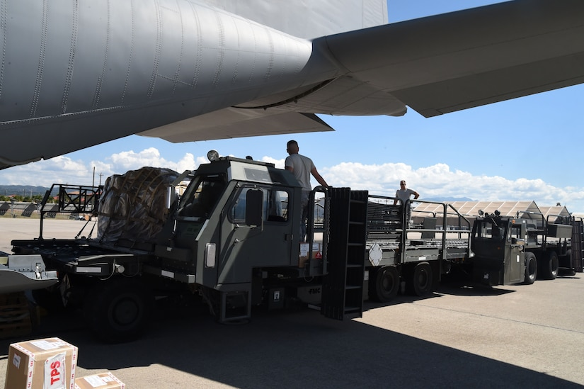 U.S. Air Force members assigned to the 612th Air Base Squadron unload cargo from a U.S. Air Force C-130J Super Hercules cargo aircraft on Soto Cano Air Base, Honduras, Jan. 7, 2016. The cargo was delivered  by use of the Denton Program, a program created to allow donated humanitarian goods the ability to use space available on military cargo aircraft. (U.S. Air Force photo by Martin Chahin/Released)