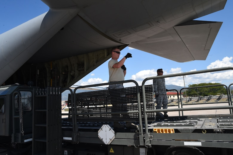 U.S. Air Force Staff Sgt. Dale Periman, 612th Air Base Squadron, gives directions to a driver while unloading cargo on Soto Cano Air Base, Honduras, Jan. 7, 2016. The cargo was delivered  by use of the Denton Program, a program created to allow donated humanitarian goods the ability to use space available on military cargo aircraft. (U.S. Air Force photo by Martin Chahin/Released)