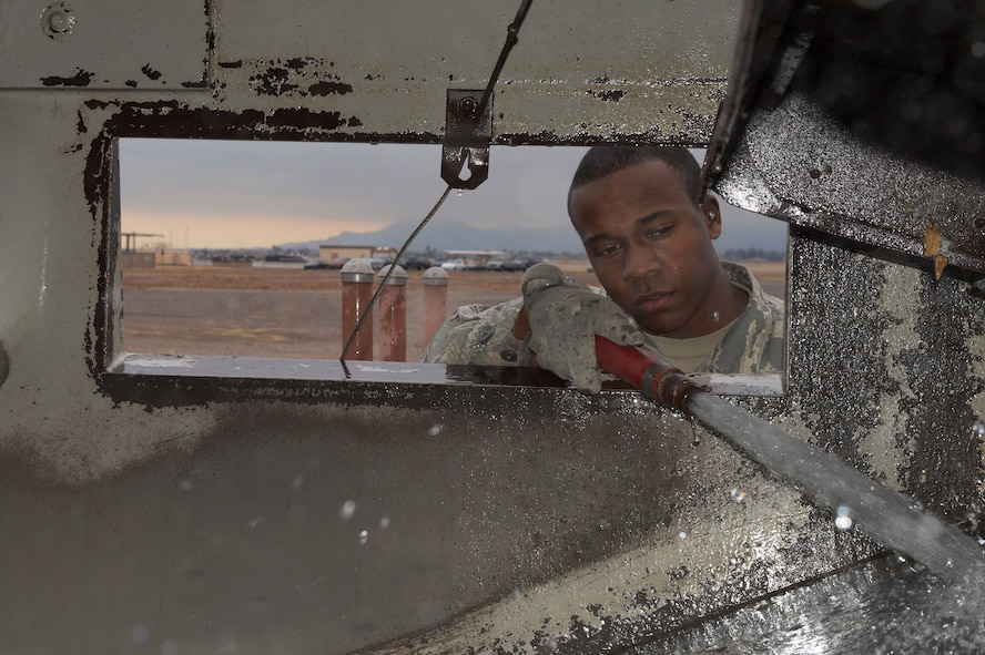Airman 1st Class Demetrius Smith, 56th Civil Engineer Squadron heavy equipment operator, watches to make sure the interior gets clean while spraying out the street sweeper at Luke Air Force Base, Ariz., Jan. 5, 2016. (U.S. Air Force photo by Senior Airman James Hensley)